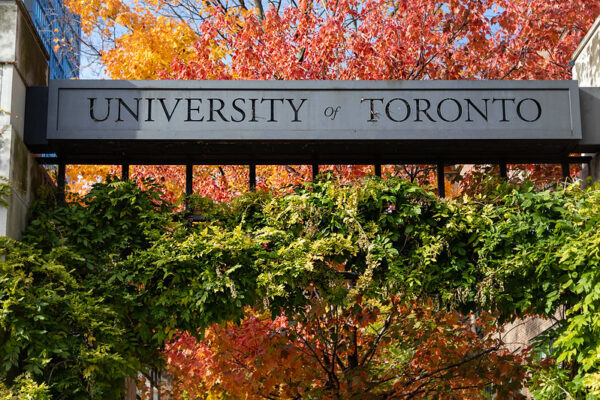 U of T signage in front of trees in fall colours.
